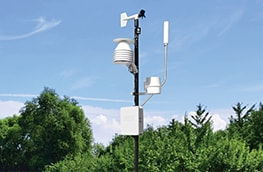 A weather station with a blue sky and green trees in the background