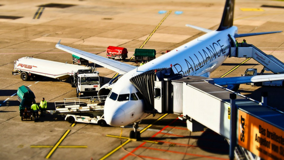 An airplane at the terminal with ground crew loading baggage