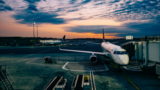 A picture of an airplane at a terminal at an airport with a pretty multicolored dusk sky