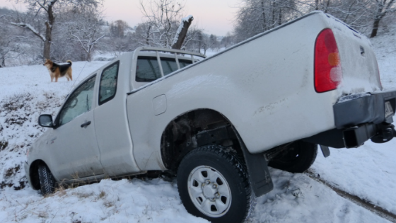 A white pickup truck stuck in a snowy ditch