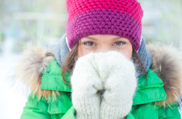 Girl with hat, mittens, and jacket outdoors during the winter