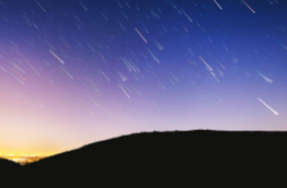 A night sky with a meteor shower with a dark hill in front