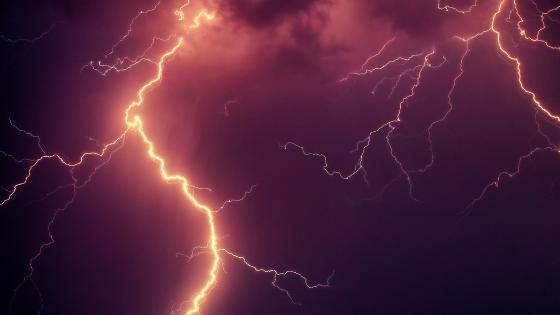 Warm flashes on lightning set against a darkish purple sky