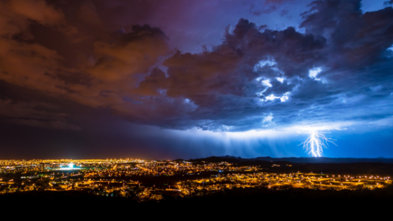 A lit up city view taken from a high elevation with a thunderstorm overhead, complete with bright lightning strikes
