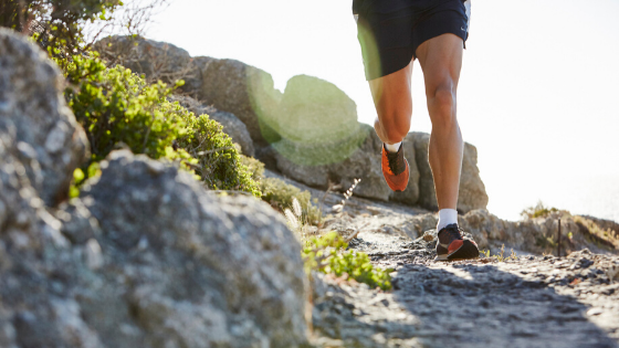 trail runner with sneakers running on a rocky path