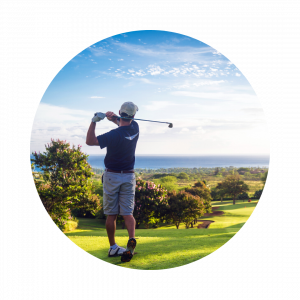 A male golfer finishing his swing at a well maintained golf course