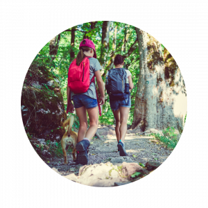 Two young girls walking on a wooded path