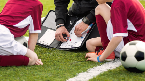 coach with soccer players drawing up a play