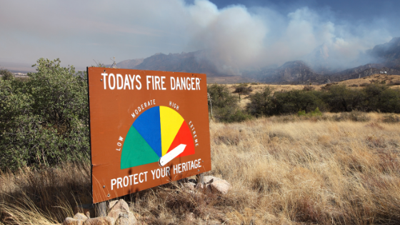 """Fire danger sign in the """"high"""" position while a wildfire burns behind it in the mountains"""