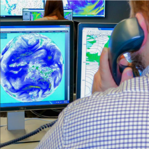 Meteorologist looking at the weather on computer screens, on the phone with a client for meteorological services