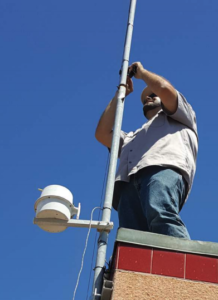 An Earth Networks field technician installing an Earth Networks weather station