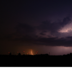 Evening thunderstorms and a wind farm with large wind turbines with red lights in the distance